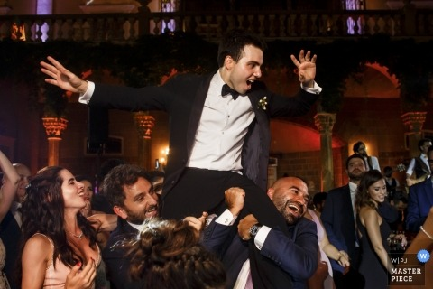 Wedding photo of the groom being lifted on the dance floor during a reception at Sursock Palace in Beirut.