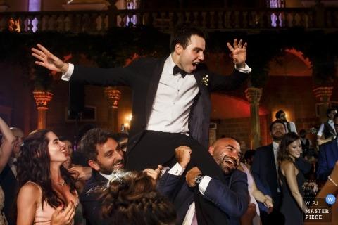 Trouwfoto van de bruidegom die op de dansvloer wordt opgetild tijdens een receptie in Sursock Palace in Beiroet.