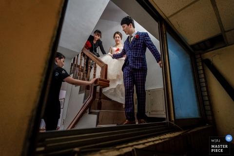 Hochzeitstagphotographie der Braut, die den Arm des Bräutigams hält, um die Treppe in der alten Wohnung ihrer Eltern in Taiwan hinunter zu gehen.