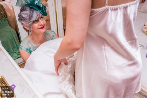 La mère de la mariée aide à mettre la robe tout en se préparant pour la cérémonie de mariage à Parroquia de San Juan.