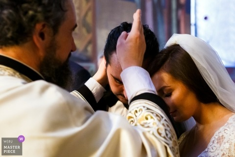 Braut und Bräutigam erhalten den Segen vom Priester während ihrer orthodoxen Hochzeitszeremonie an der St. Apostoli-Kirche, Rumänien.