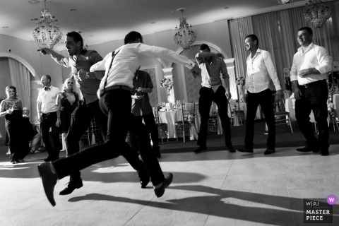 Pan młody i drużbowie tańczą podczas przyjęcia na Bliss Event - fotografia ślubna w czerni i bieli.