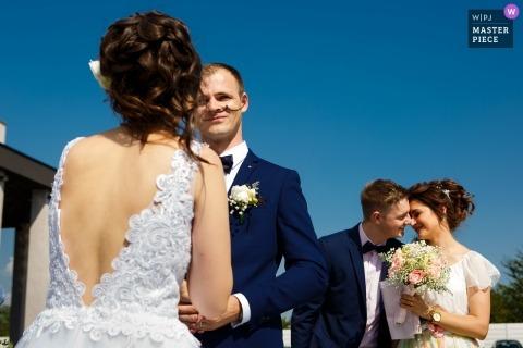 Photo de mariage du marié réagissant pendant la cérémonie tandis que les parrains deviennent émus lors des événements Bliss en Roumanie.