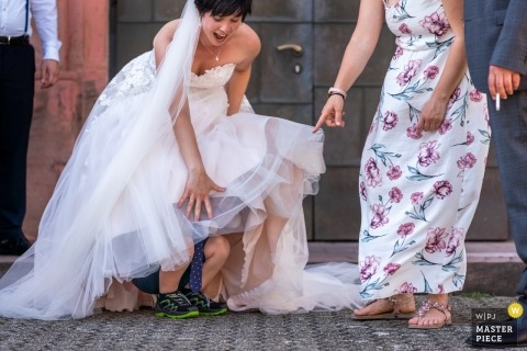 A child is unexpectedly going under the wedding dress surprising the bride and everybody there at Zell am Harmersbach.