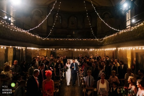 Wiltons Music Hall wedding photo | Bride walks down the aisle with her father in an old converted Victorian music hall