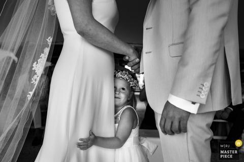 Dochter van de bruid en bruidegom geeft haar moeder een knuffel tijdens de huwelijksgeloften bij Golfclub Méan.