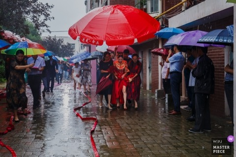 Shandong Huwelijksfotografie - Verwelkom de bruid in de regen onder paraplu's op een trouwdag.