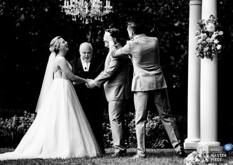Le meilleur homme essuie de la sueur de son front au milieu d'une chaude cérémonie de mariage d'été à Separk Mansion.