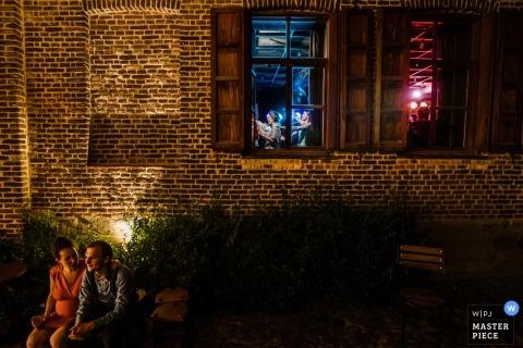 Photographie de mariage de La Petite Fabriek d'un couple en train de profiter d'une pause à l'extérieur du hall de réception pendant que vous apercevez la fête à l'intérieur.