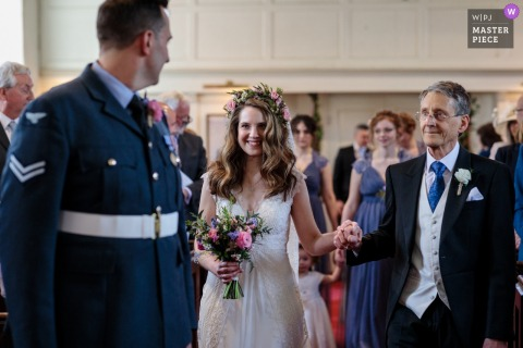 Hayne House, Kent, Royaume-Uni. Photo de la mariée qui arrive dans l'allée avec son père pour rencontrer son futur mari.