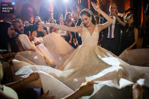 Photographie de mariage Castello Odescalchi de La fête libanaise sur le plancher de danse avec la mariée et sa grande robe