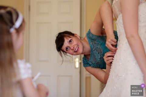 La demoiselle d'honneur prépare les boutons de la robe des mariées pendant que sa fille regarde - Photographie de mariage de Broome Park, Barham, Kent, Royaume-Uni