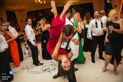 Una dama de honor se voltea boca abajo en la pista de baile. - Fotografía de bodas de Casa Cien, San Miguel del Allende, México
