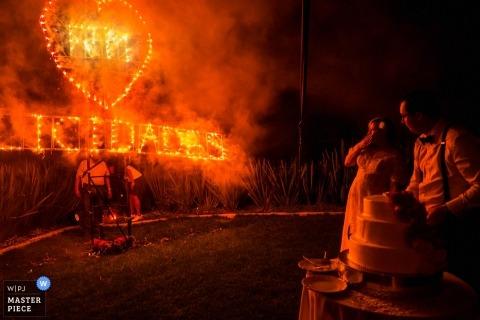 Casa Cien, San Miguel del Allende, Meksyk fotograf ślubny | Panna młoda i pan młody są zszokowani wystrojem ognia podczas cięcia ciasta.