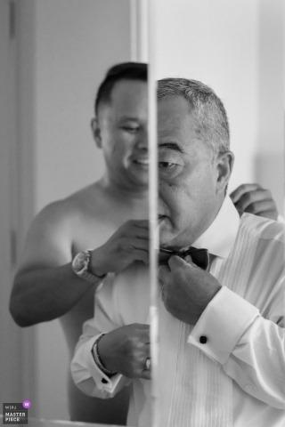 Ojciec panny młodej jest asystowany w krawacie przez członka rodziny na tym ślubie w Los Angeles w Ayara.