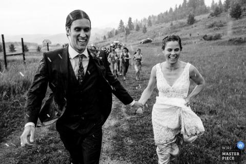 Rocky Creek Farm - Bozeman, Montana trouwfoto van bruid en bruidegom die na de ceremonie door de regen rennen.
