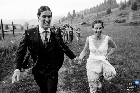 Rocky Creek Farm - Bozeman, Montana, foto de la boda de los novios corriendo bajo la lluvia después de la ceremonia.