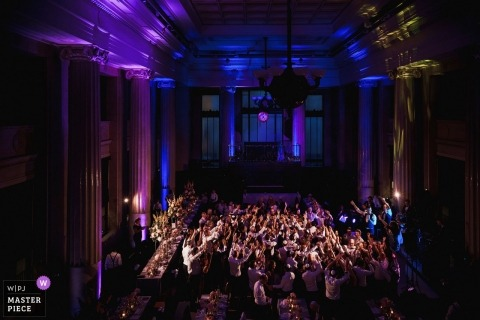 London reception venue photograph of the guests in the hall with brilliant colors of blue and purple.