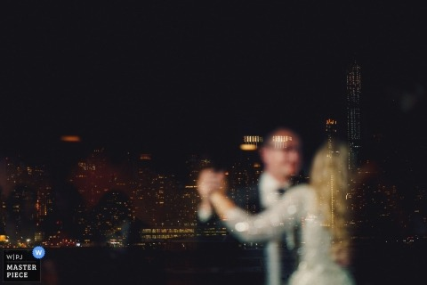 New York wedding photo of a first dance taken through a window reflecting the New York sky line.