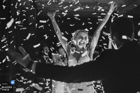 Black and white wedding reception photo of confetti flying just seconds after guests popped a ticker-tape bomb on the first dance