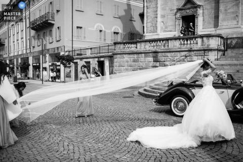 Bruidsmeisjes helpen de bruid met haar sluier op straat bij haar Bellinzona-huwelijk.
