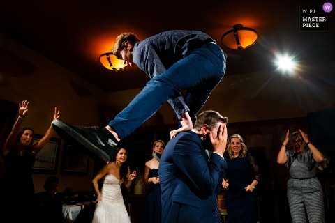 Uley's Cabin, Crested Butte wedding reception photo of a man leaping over the head of another man.