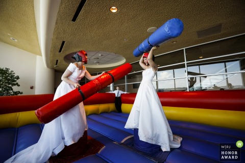 Monona Terrace, Madison, WI wedding venue photo | The brides partake in some pre-ceremony bounce house jousting at their wedding.
