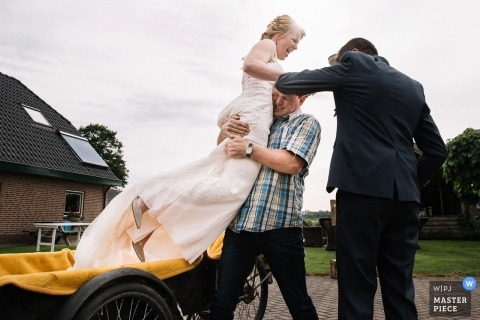 Netherlands Home bride getting ready images - Father of the bride gets bride out of bike on wedding day.