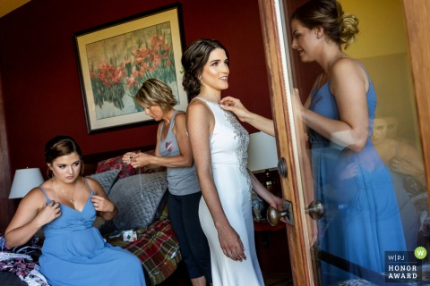 Wedding Photo - The bridesmaid places jewelry on the bride while her mother in law threads a needle to repair the dress. | Vacation Rental (VRBO). Murrieta, California.