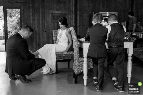 VRBO wedding photography | Vacation Rental in Murrieta, California. | The groom helps his bride with her shoes, while their boys stand at their table.