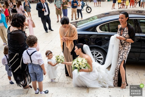 Cathedral of Syracuse wedding photography | The amazement of the little girl who receives flowers from the bride before entering the church.