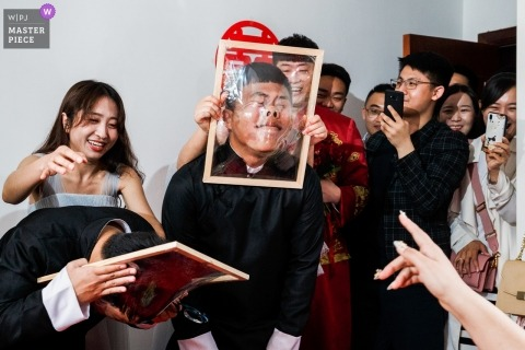 The Game Link of the Groom's Reception.  Groom is having his face smashed through a cellophane -wrapped frame for a China wedding.