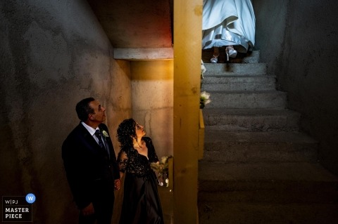 Bride ascends down the stairs, leaving the house to attend her Reggio Calabria wedding.