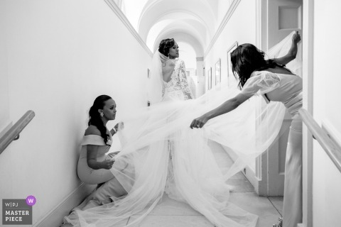 Wedding Photography at Fulham Palace of a bride having the final touches done on her dress by her bridesmaids.