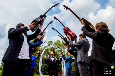 Germany wedding reportage photography | Ceremony entrance under guitars held by guests and wedding party members