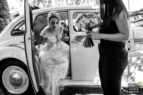 İncek Garden wedding venue arrivial picture | Bride, holding bouquet is getting out from the wedding car