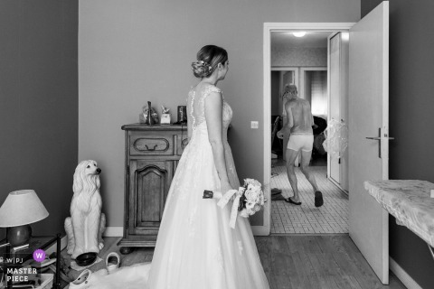 Lyon, France Wedding Reportage Photographer | A bride in her room and the father walk behind the door
