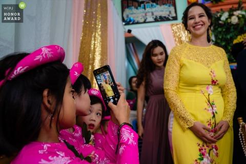 Vietnam Hochzeitsfotograf bei der Braut zu Hause: Diesen Moment habe ich festgehalten, als ein Kind einen Gast in einer Zeremonie festhielt.