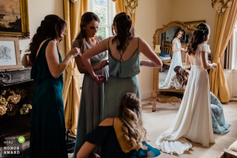 Lisnavagh House, Carlow, Ireland wedding photography | Prep finishing touches to the bride and bridesmaids.