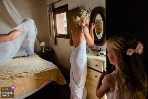 Tenuta di Papena, Tuscany, Italy Wedding Reportage Photographer - Bride about to get veil on touches up make up, flowergirl looks on from behind bedroom door.