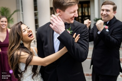 Biltmore Ballrooms Atlanta Wedding Venue Photography - Bride sneaks a clothespin on her grooms ear getting everyone a good laugh
