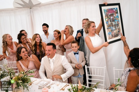 Golf Club of Mean wedding venue picture | Wedding party is laughing loud because of a photo compilation of the bride's stag weekend in Ibiza, given by the bride's father