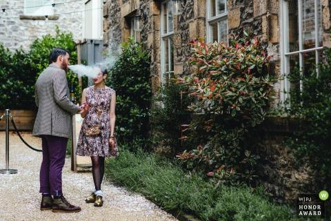Holmes Mill Cheshire UK Hochzeitsort Bild | Zwei Hochzeitsgäste haben eine Zigarette, der Mann bläst Rauch über das Gesicht der Frau
