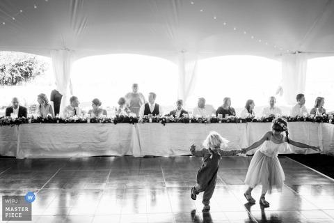 Roozengaarde Wedding Reception Photographer | Two kids run around the dance floor during wedding reception