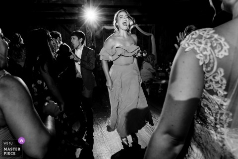 The Preserve at Chocorua in Tamworth, NH Wedding Photography | The maid of honor gets wild on the dance floor at her best friend's wedding as the bride watches