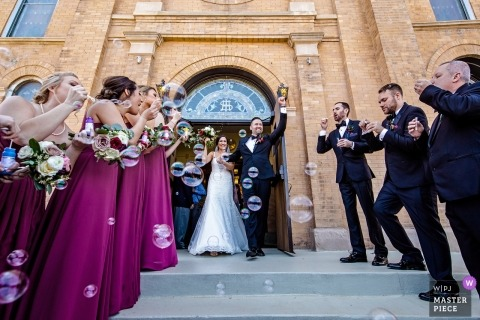 Illinois Biagio Events - Wedding ceremony photography of the bride and groom coming out of the church with friends and guests around them
