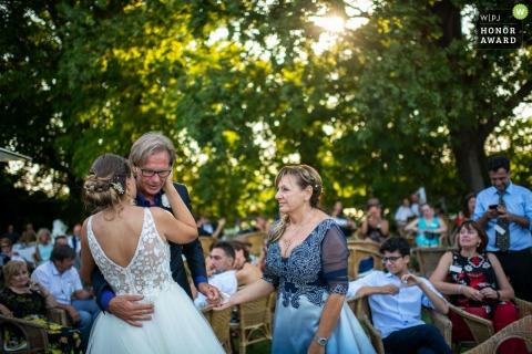 Chiesa di Rocca d'Arazzo AT / Location Villa Fiorita Castello di Annone (AT) | Wedding photo - a hug with the father and the look of the mother