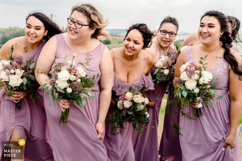 Fotografía del día de la boda en Fort Chipewyan, Alberta: dama de honor que mira a la novia venir por el pasillo durante una ceremonia al aire libre y ventosa
