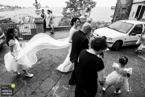 Via Guglielmo Marconi - Aci Castello wedding photography | The bride is accompanied to the church on foot, passing through the street of the historic center, on the famous Riviera of the Cyclops in Sicily.
