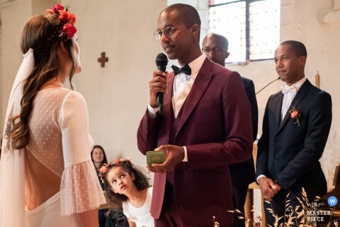 Church, Beaucouzé 49 France Wedding Photographer | The groom pronounces his vows and his niece is watching him.